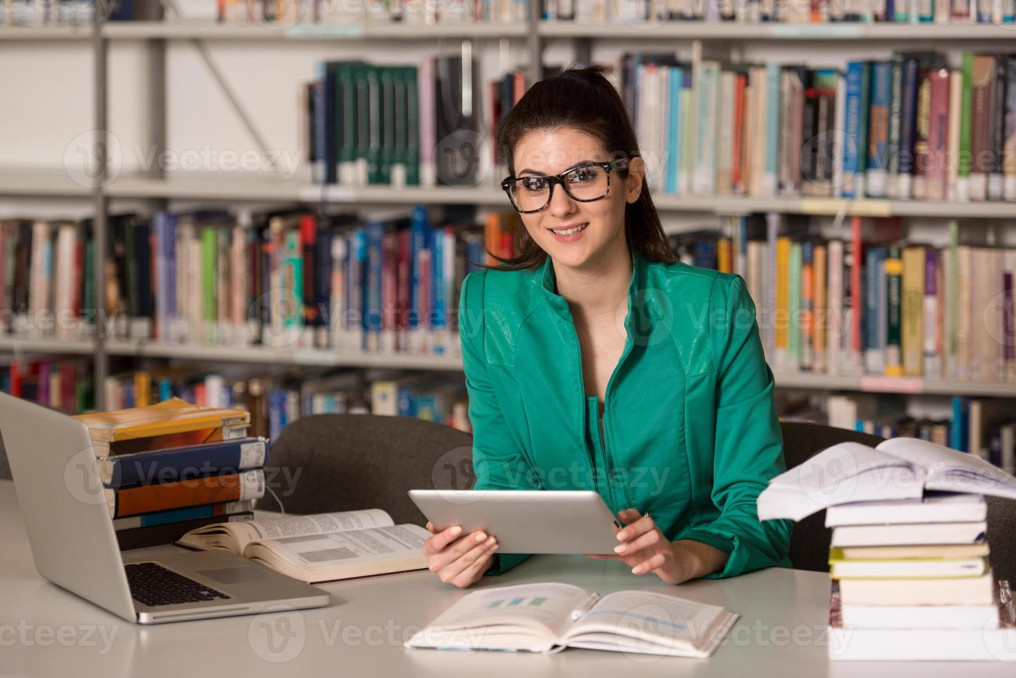 Happy Female Student With Laptop In Library photo