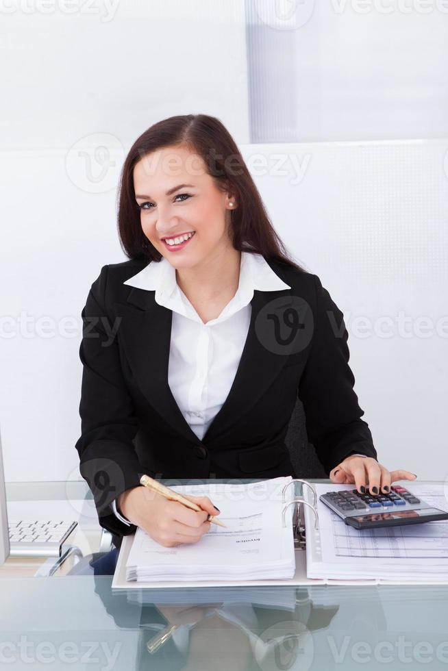 Happy Businesswoman Calculating Tax photo