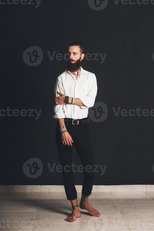 joven guapo en camisa blanca sobre fondo negro foto