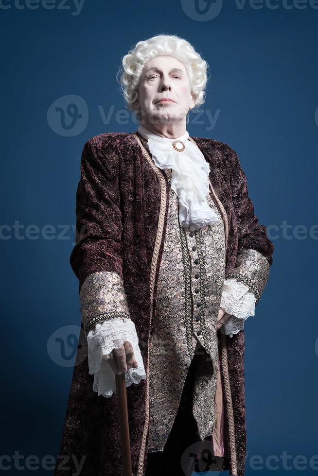 Retro baroque man with white wig standing with walking stick. photo