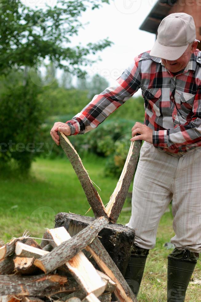 hombre cortando leña foto