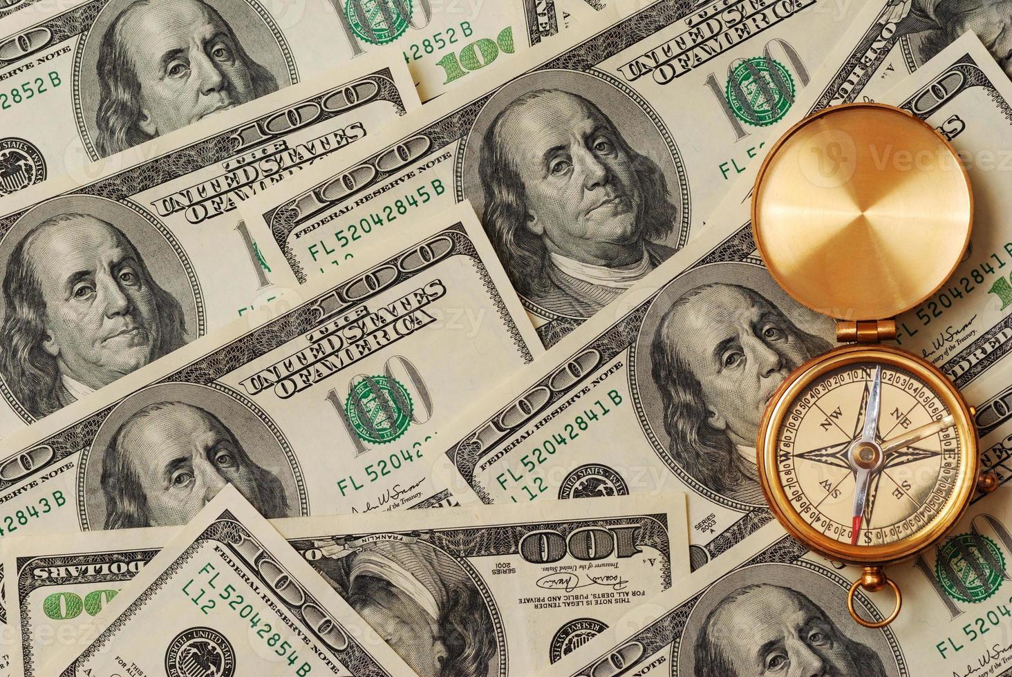 Antique compass over money photo