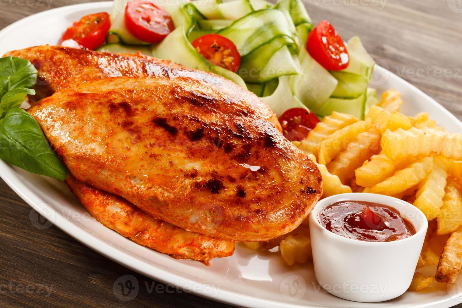 Filetes de pollo a la parrilla, papas fritas y verduras sobre fondo blanco. foto