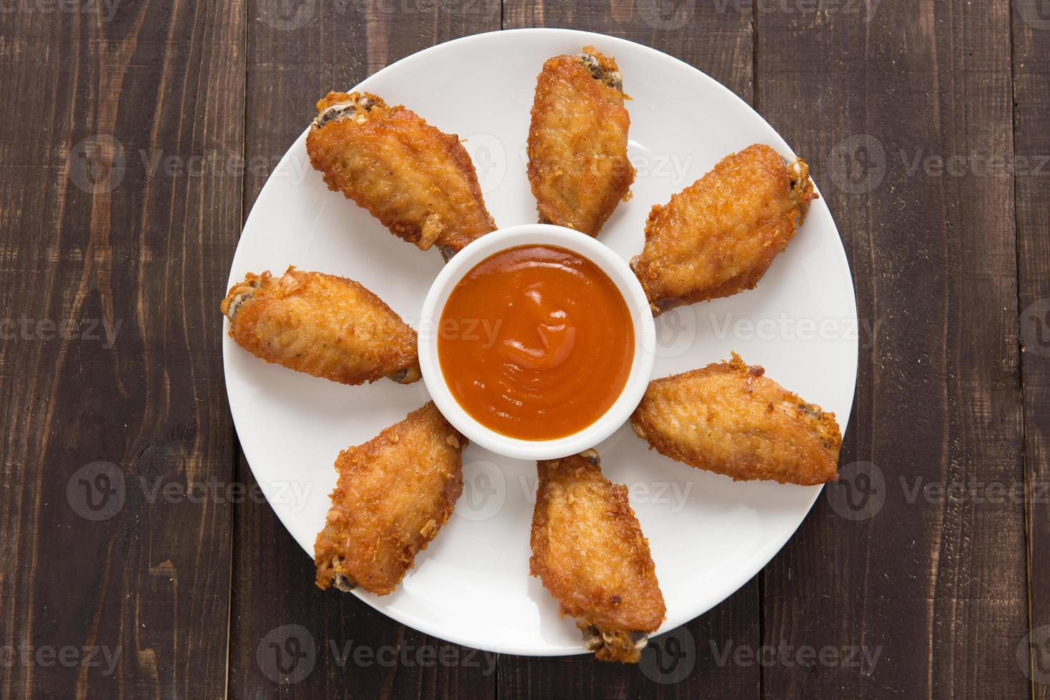 Top view fried chicken wings on wooden background photo