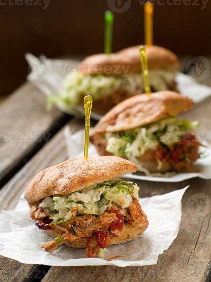 Three pulled pork sandwiches on paper on wooden surface photo