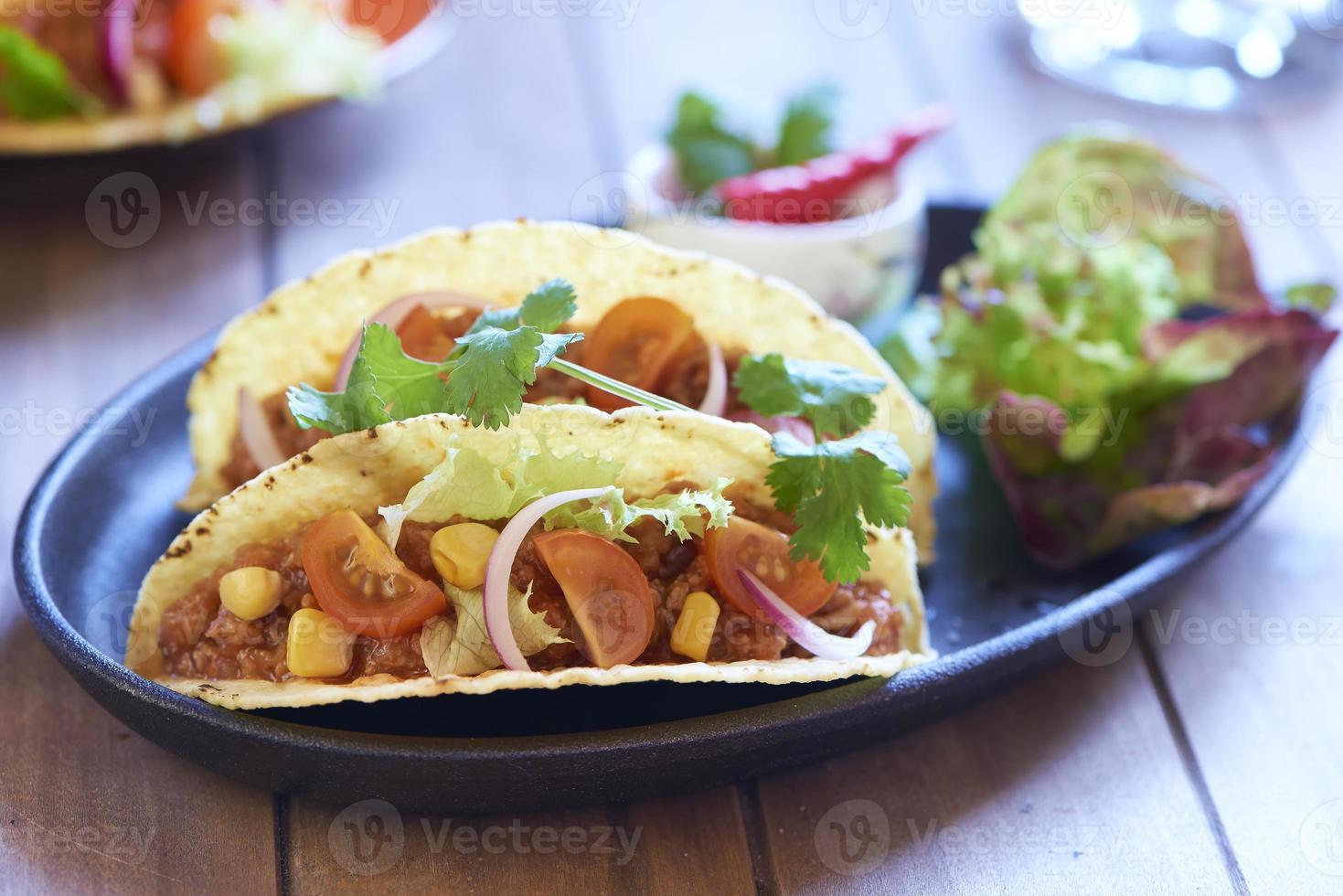plato con taco, ensalada y salsa de tomate foto