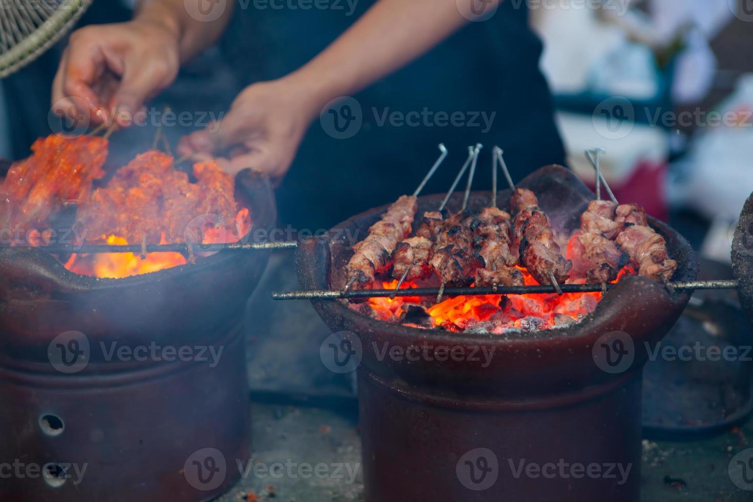 Hombre cocinando satay klatak jogja en carbón caliente foto