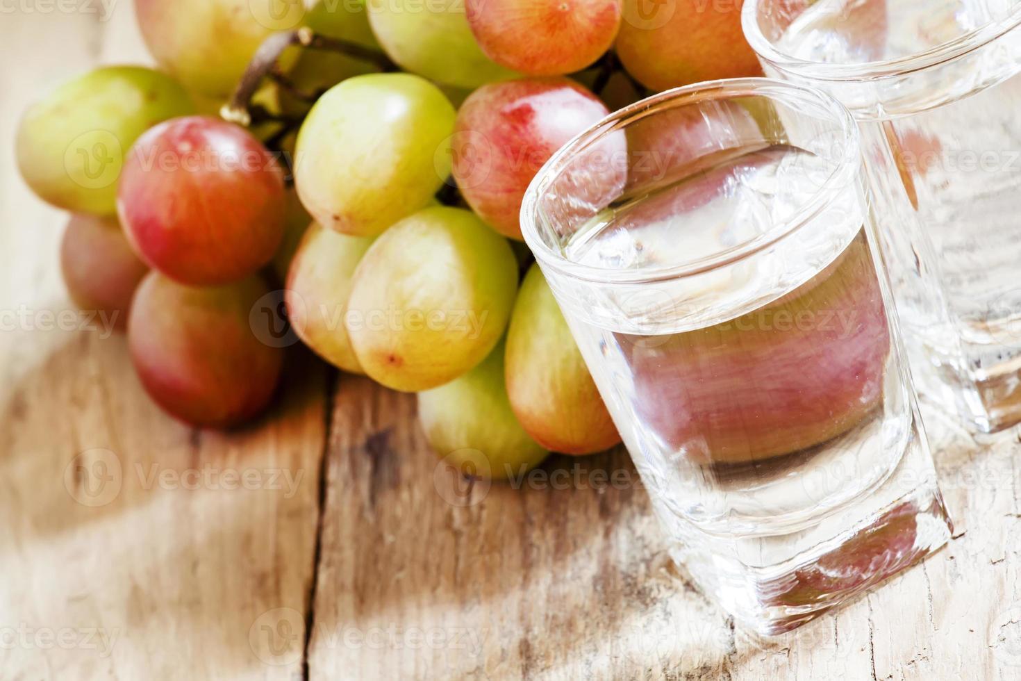 grappa en un vaso pequeño y uvas maduras foto