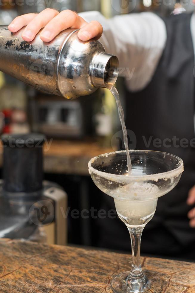 barman en el trabajo, preparando cócteles. vertiendo margarita en copa de cóctel. foto