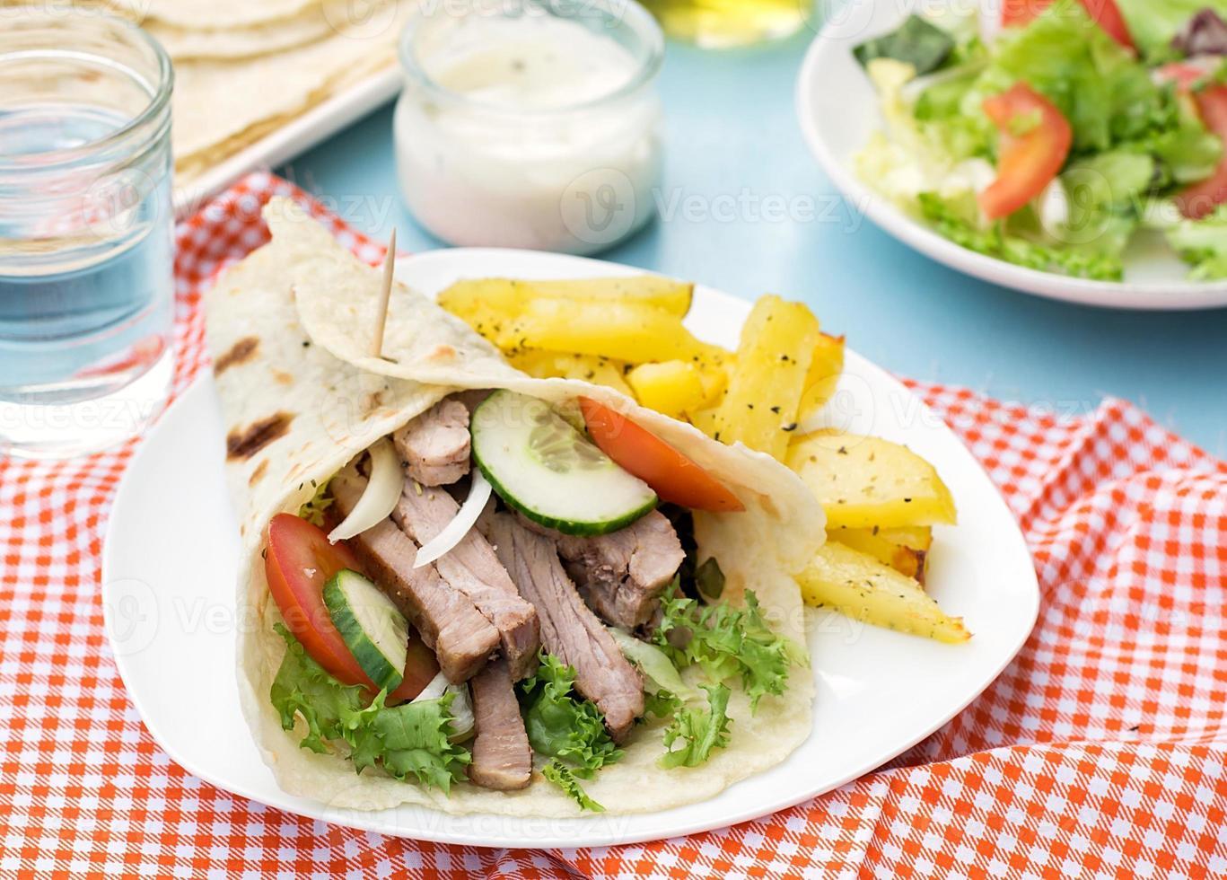 giroscopios griegos con carne de cerdo, verduras y pan de pita casero foto