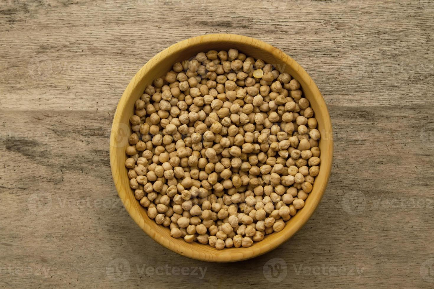 bunch of chickpeas in bowl on old wooden background photo