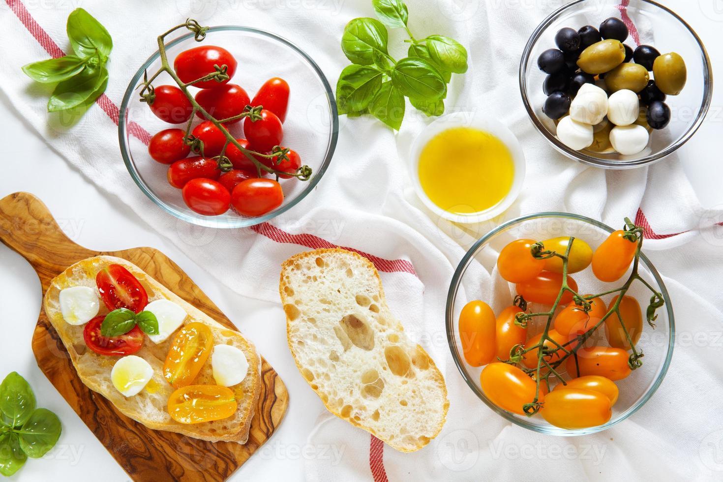 bruschetta con tomates cherry amarillos y rojos, albahaca fresca, gre foto