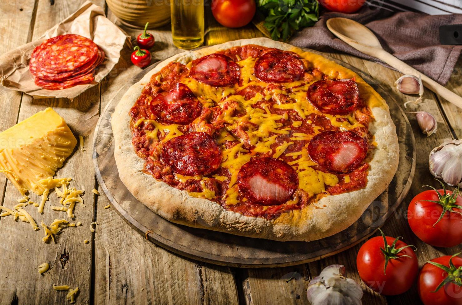 Rustic salami pizza with cheddar cheese and chorizo photo