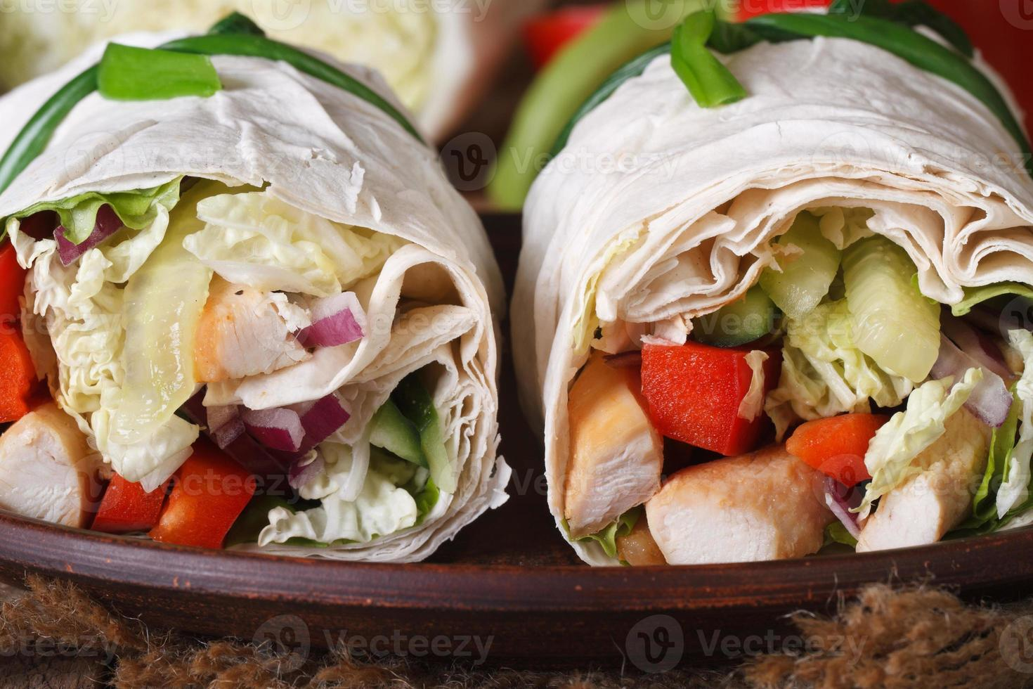 Rollo de pan de pita con pollo y verduras macro, horizontal foto