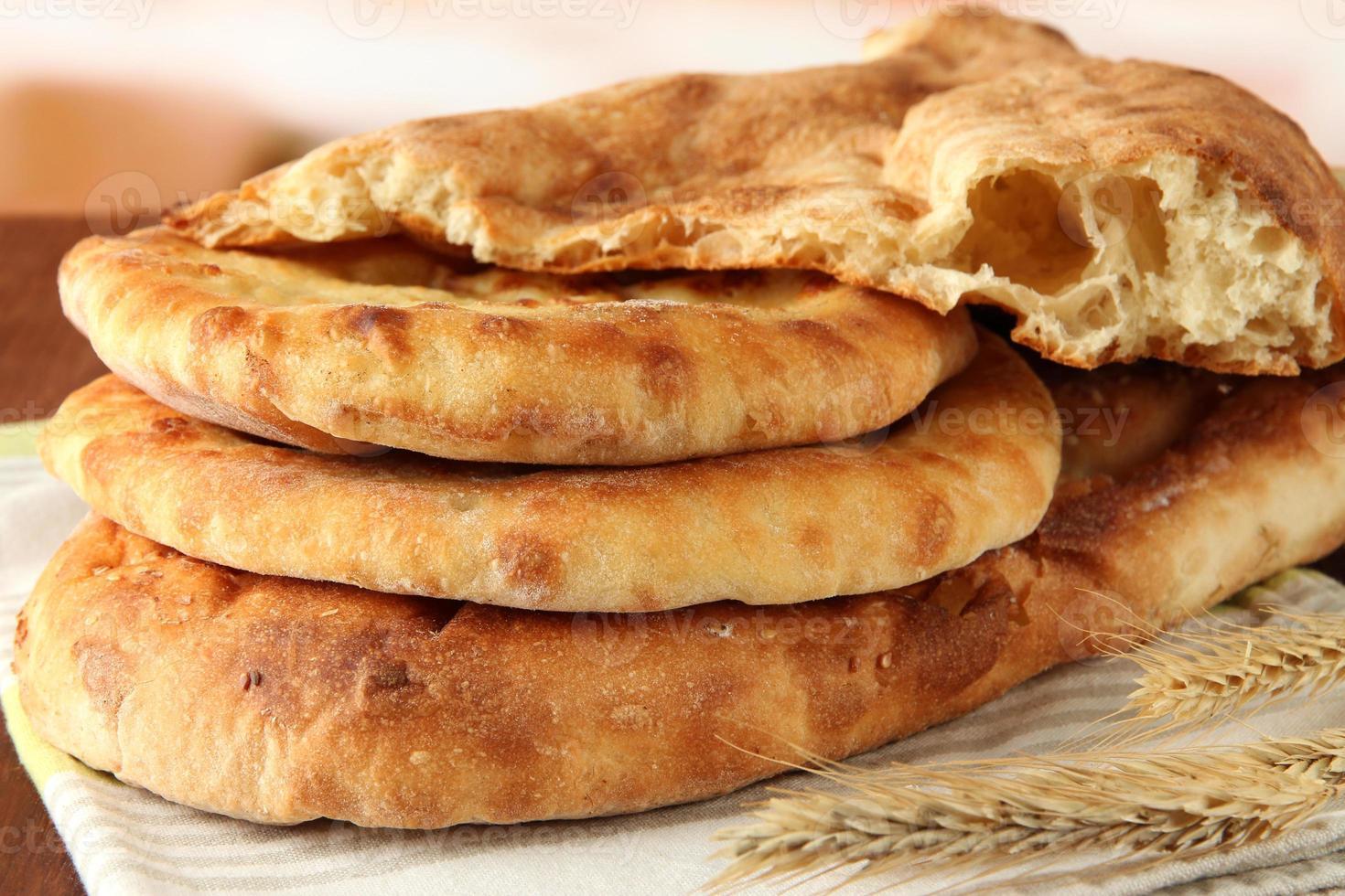 pães pita com picos na mesa, fundo brilhante foto