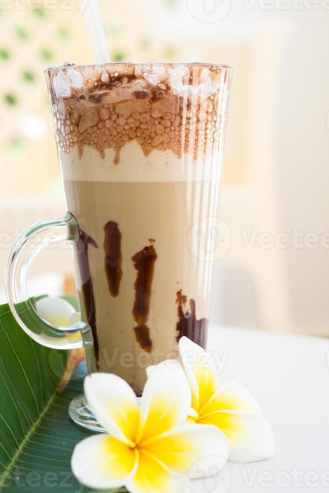 bebida de café helado frappe con plumeria foto