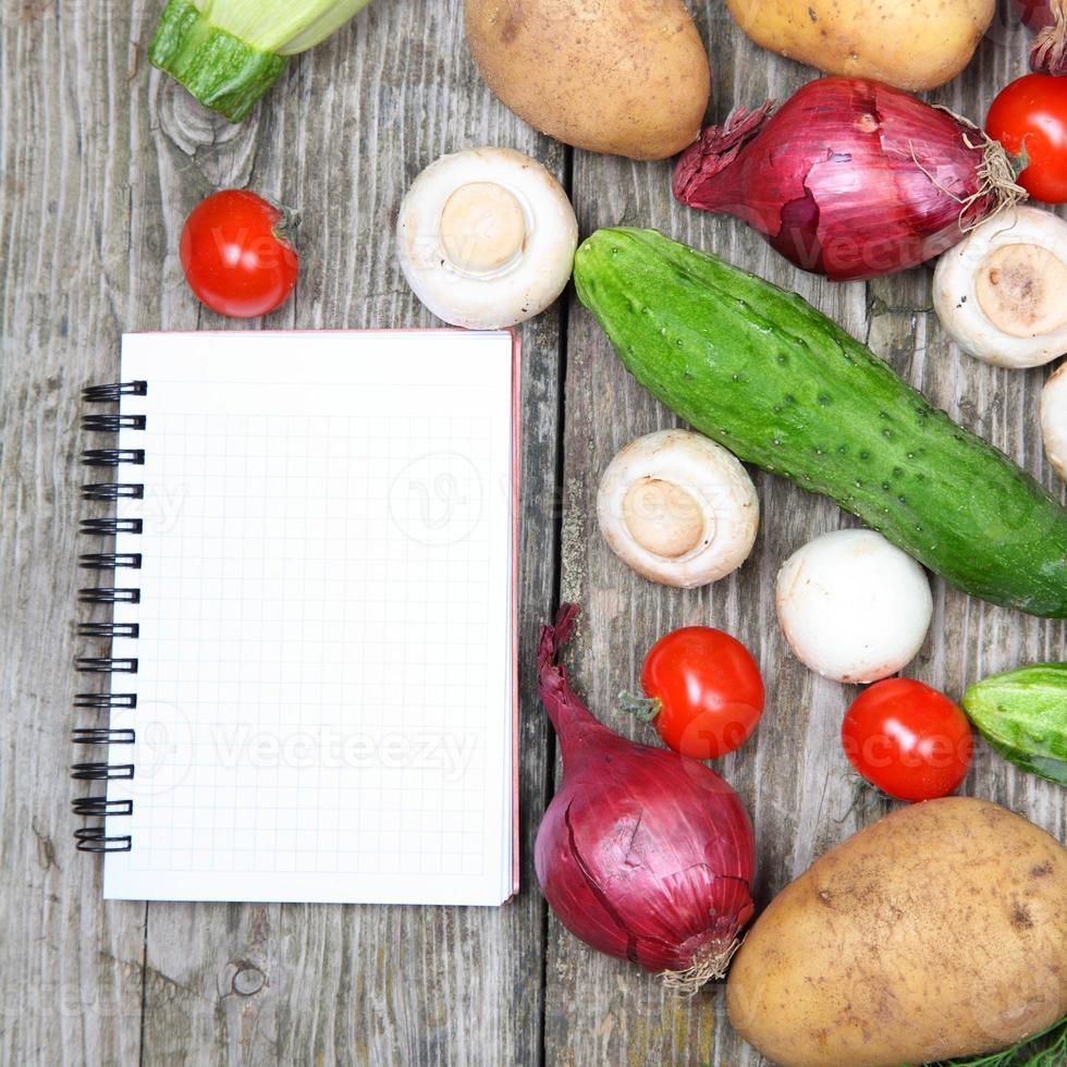 legumes frescos e um caderno de receitas foto