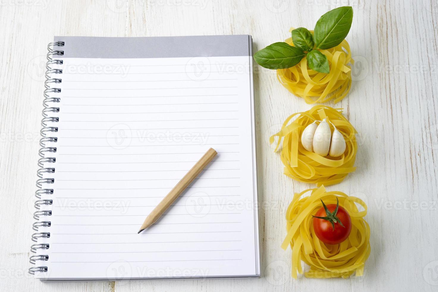 macarrão com livro de receitas em branco foto