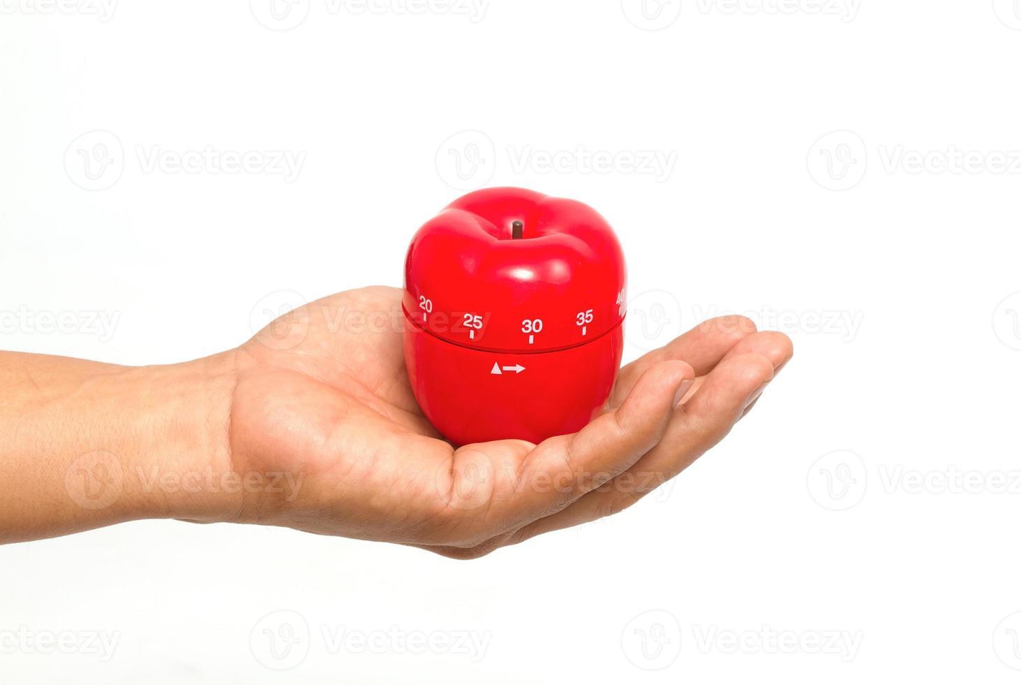 La mano del chef con un temporizador de manzana foto