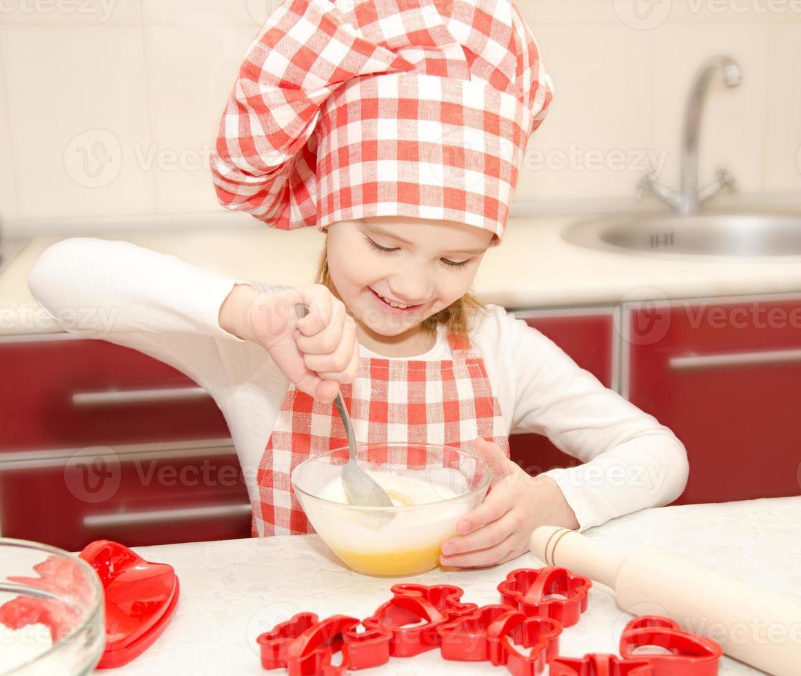 Niña sonriente con chef hat revolviendo masa para galletas foto