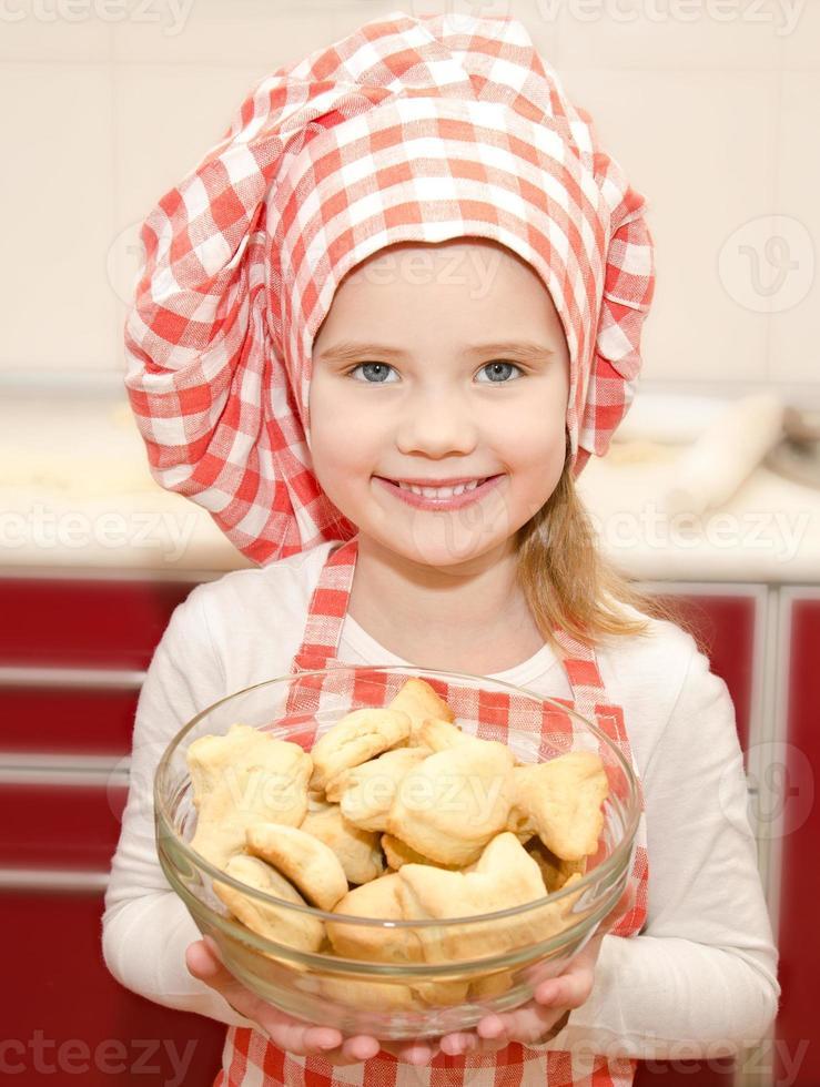 Niña con gorro de chef sosteniendo tazón con galletas foto