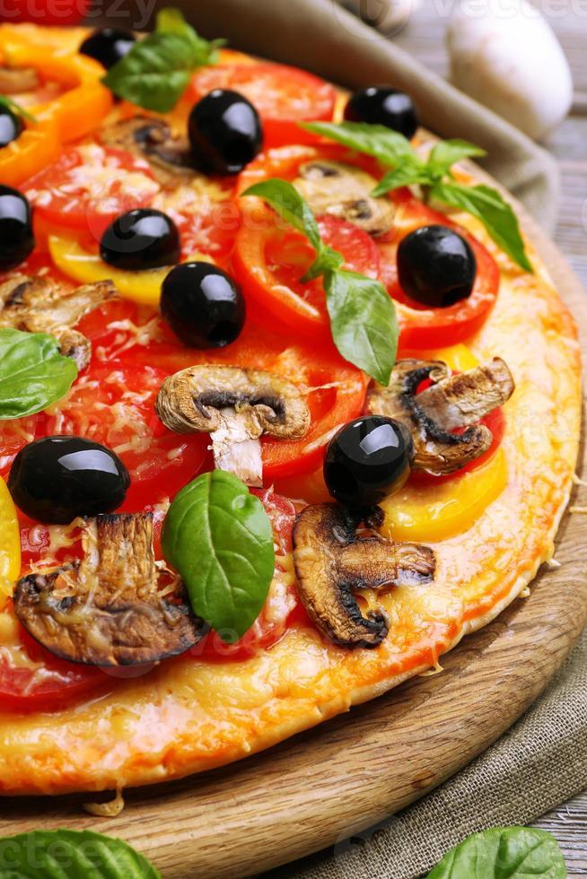 deliciosa pizza servida en mesa de madera foto