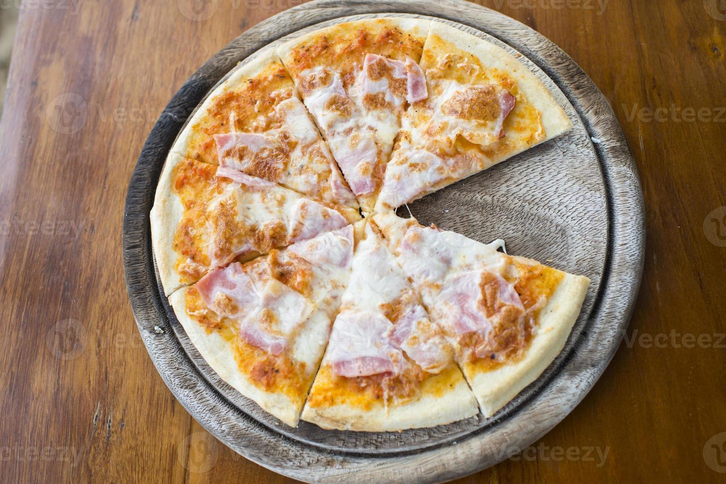 Jamón de pizza casera en mesa de madera. foto