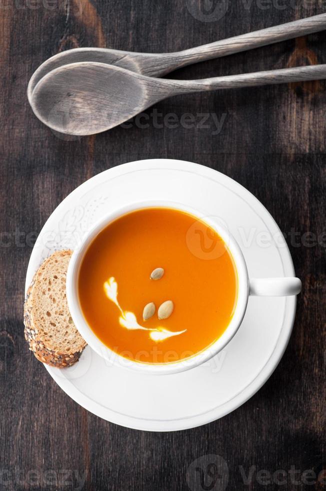 sopa de abóbora com sementes de abóbora em caneca branca foto