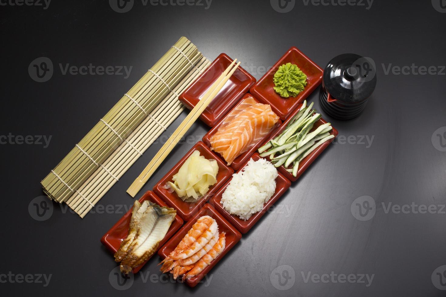 ingredientes para sushi: rodajas de salmón, pepino, arroz, wasabi y jengibre foto