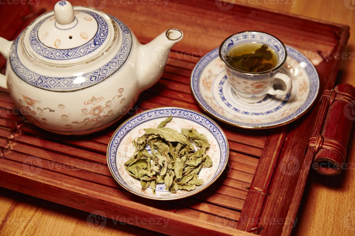 Chinees theeservies, met blaadjes van groene thee foto