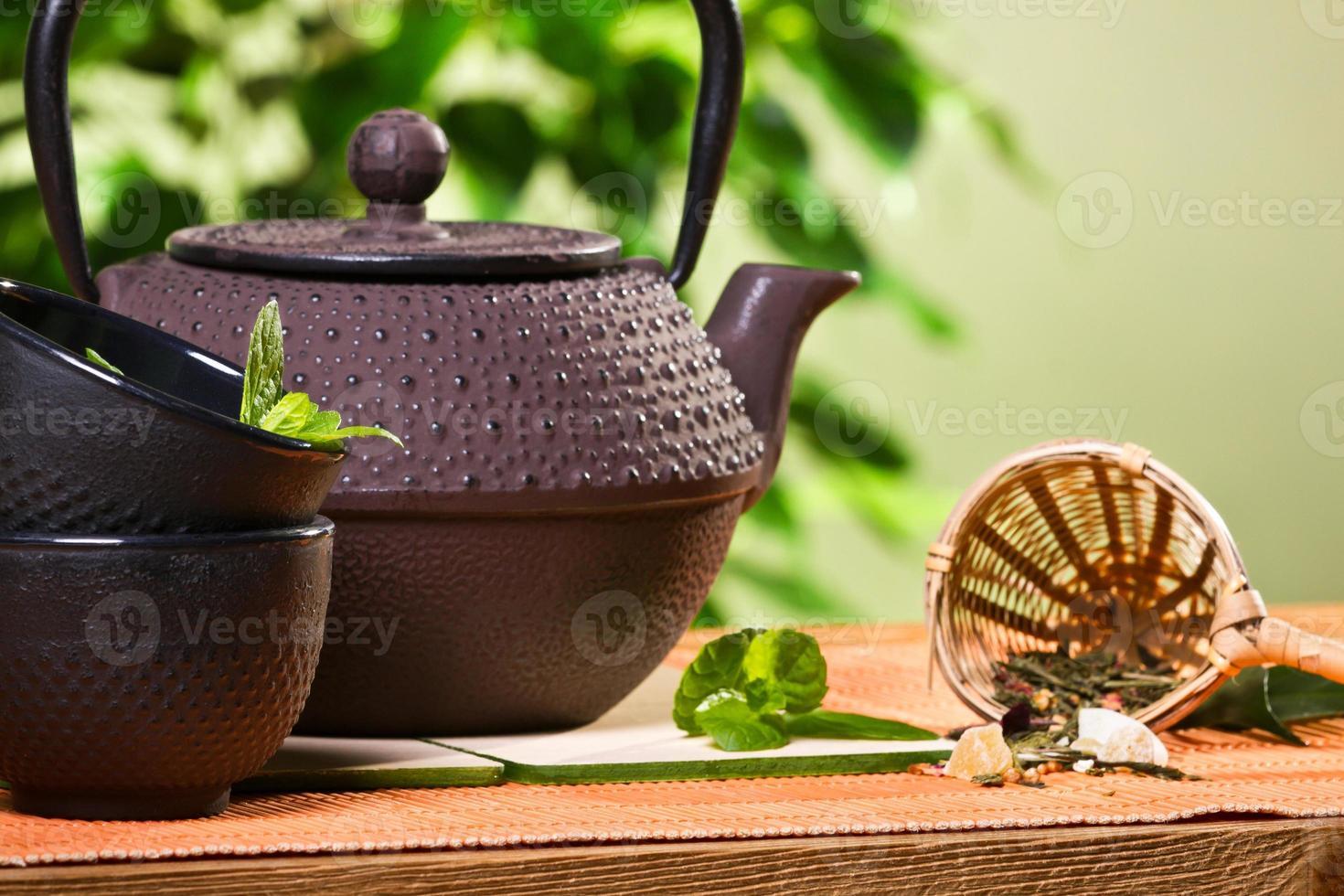 tetera con taza y hojas de menta fresca foto