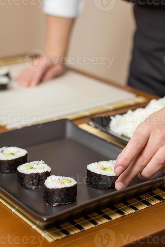 Chef mujer colocando rollos de sushi japonés en una bandeja foto