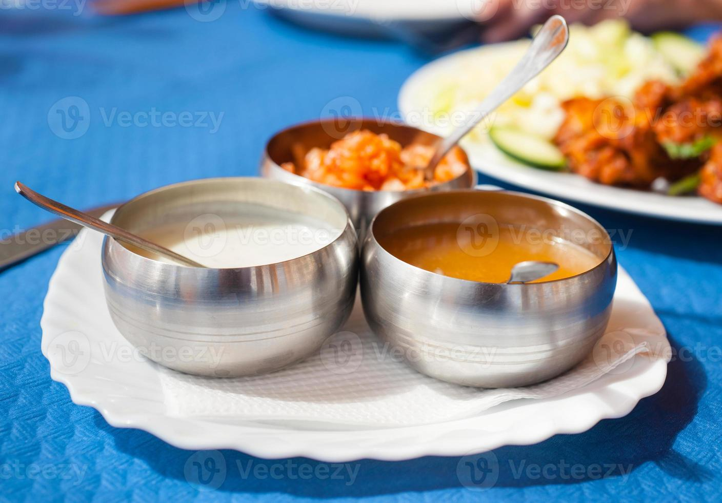 three bowls with Indian sauces to salad dressings photo