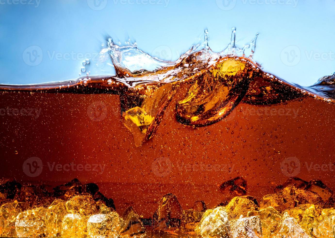 Cola with Ice. Splash and bubbles photo