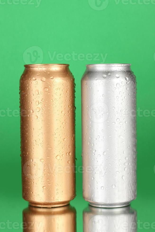 Aluminum cans with water drops on green background photo