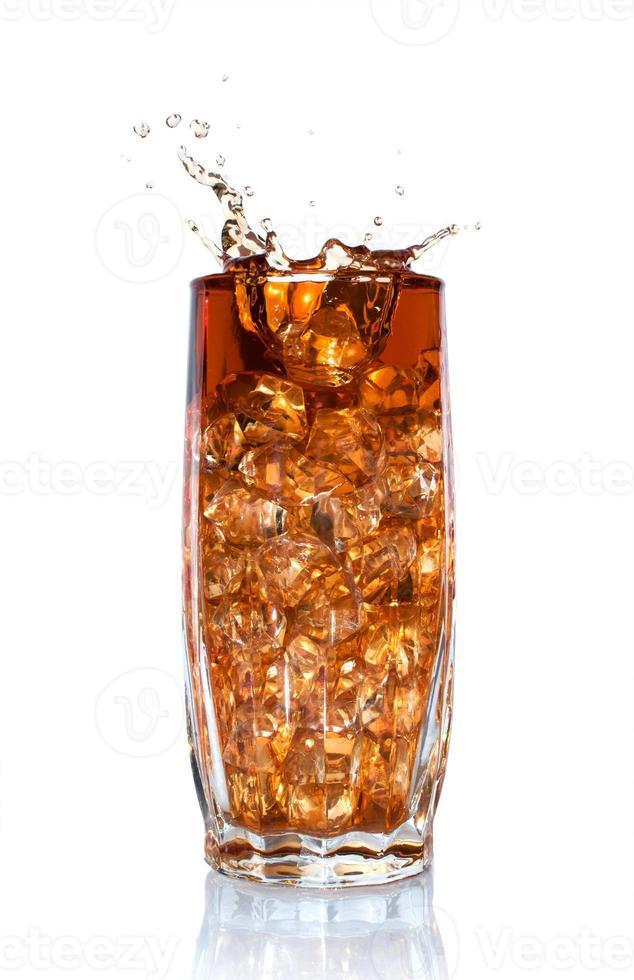 salpicaduras de cola en vaso con hielo foto