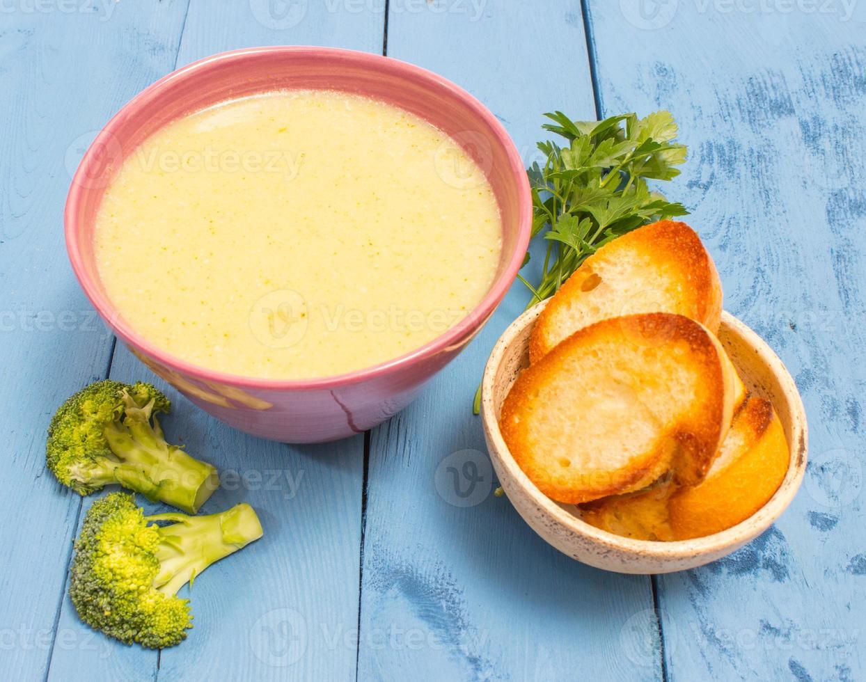 sopa de brócoli en un tablero azul foto