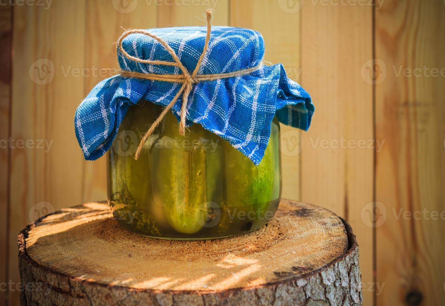 Jar pickled cucumbers wooden stump photo