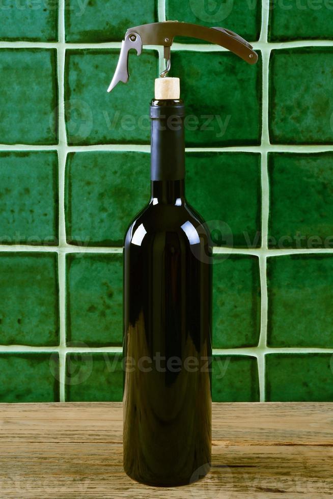Botella de vino tinto con sacacorchos sobre fondo verde. foto