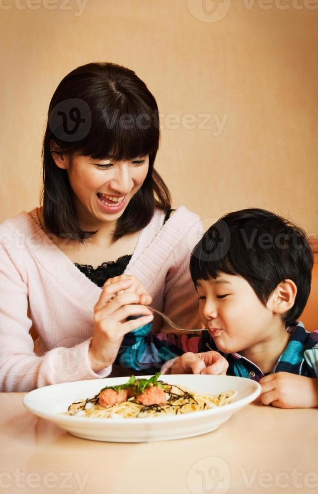 Mother and son happily eating spaghetti at the table photo