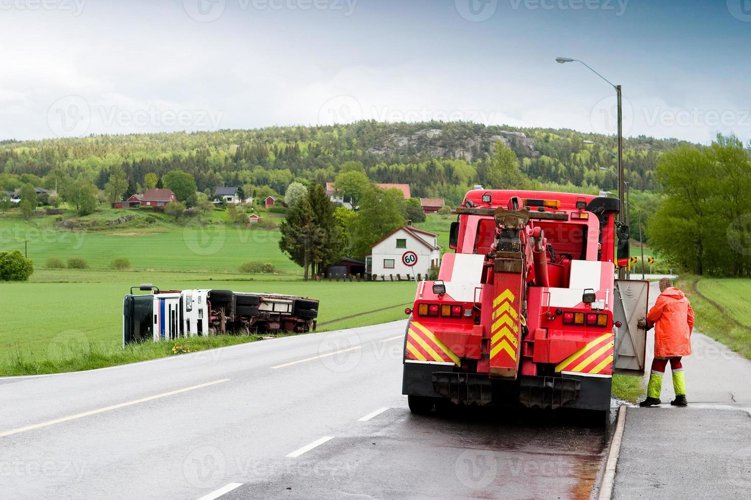 una grúa roja limpiando la carretera de un pueblo rural foto
