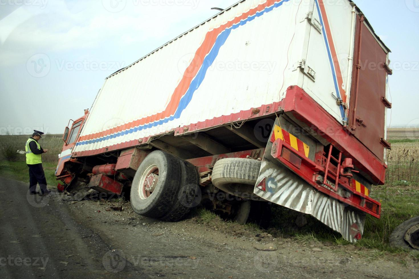 Truck lying in a ditch with policeman investigating photo