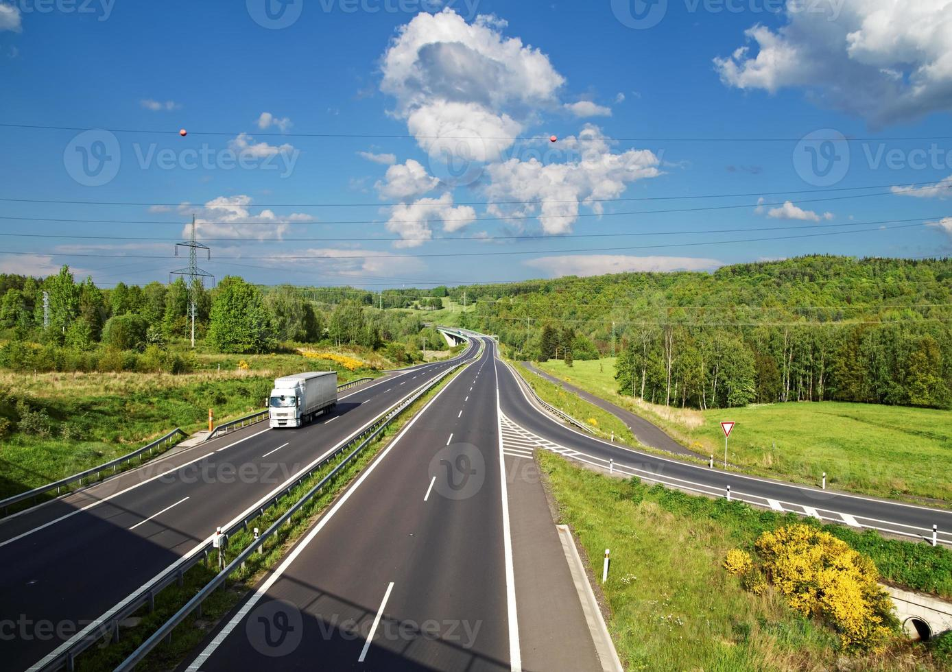 Access road to the asphalt highway between forests. White truck. photo