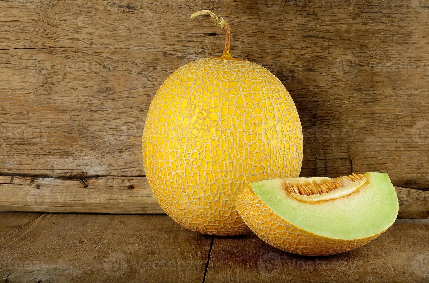 Yellow cantaloupe melon on the wooden background photo