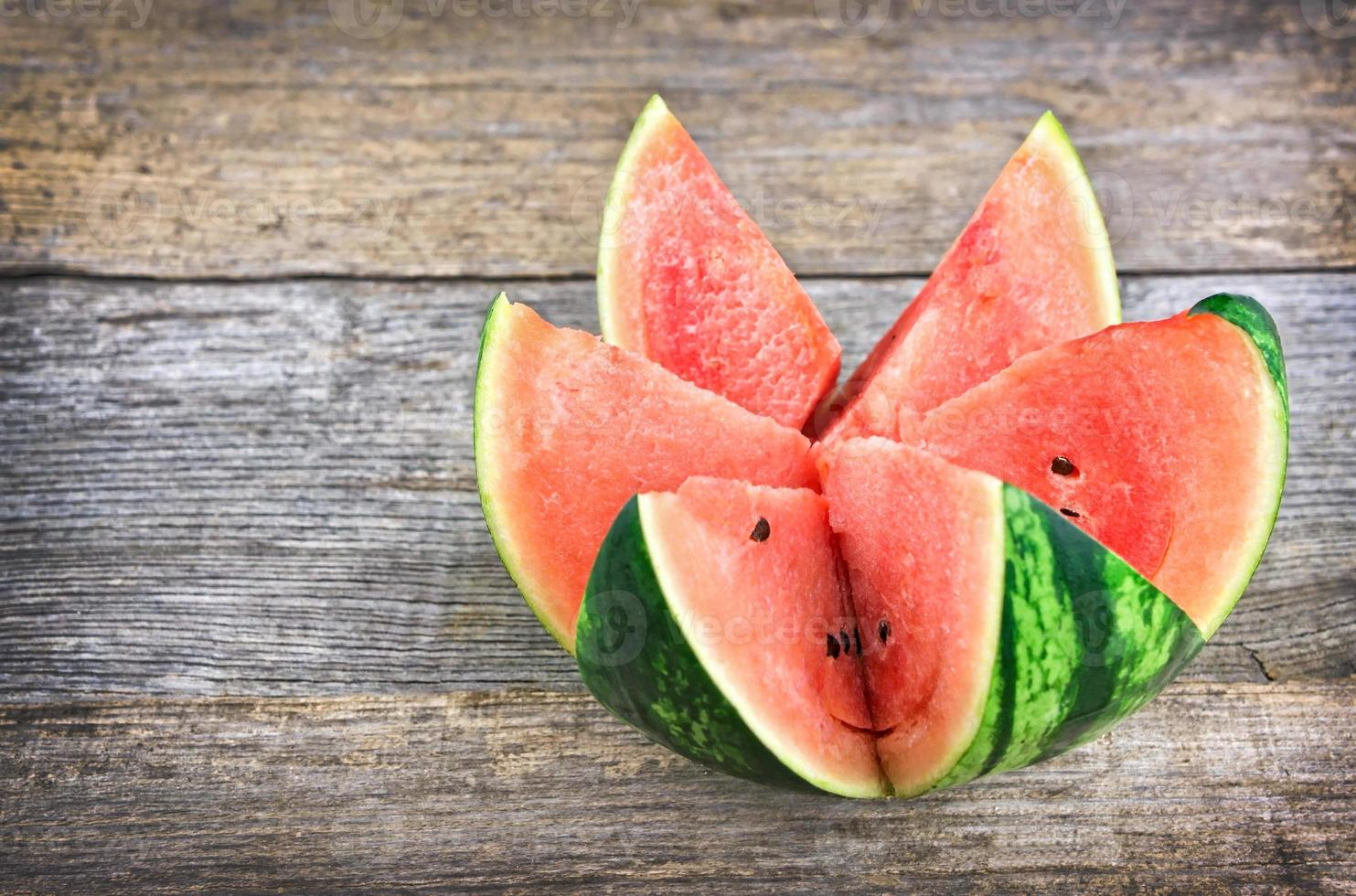 Fresh watermelon on rustic wooden table photo