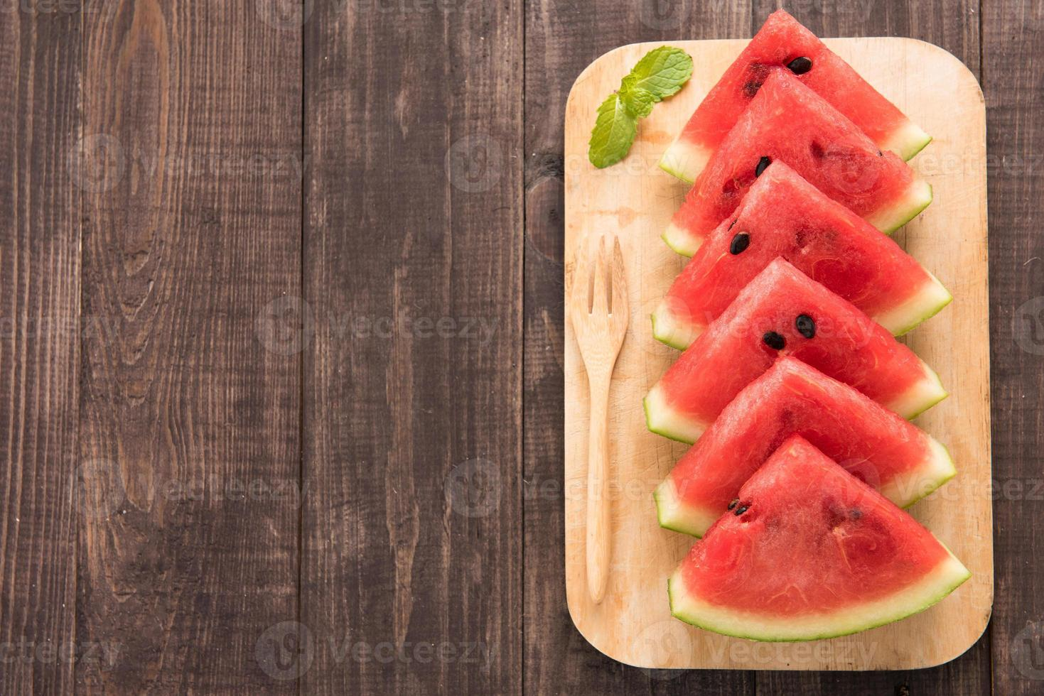 Fresh watermelon pieces placed on wooden background photo