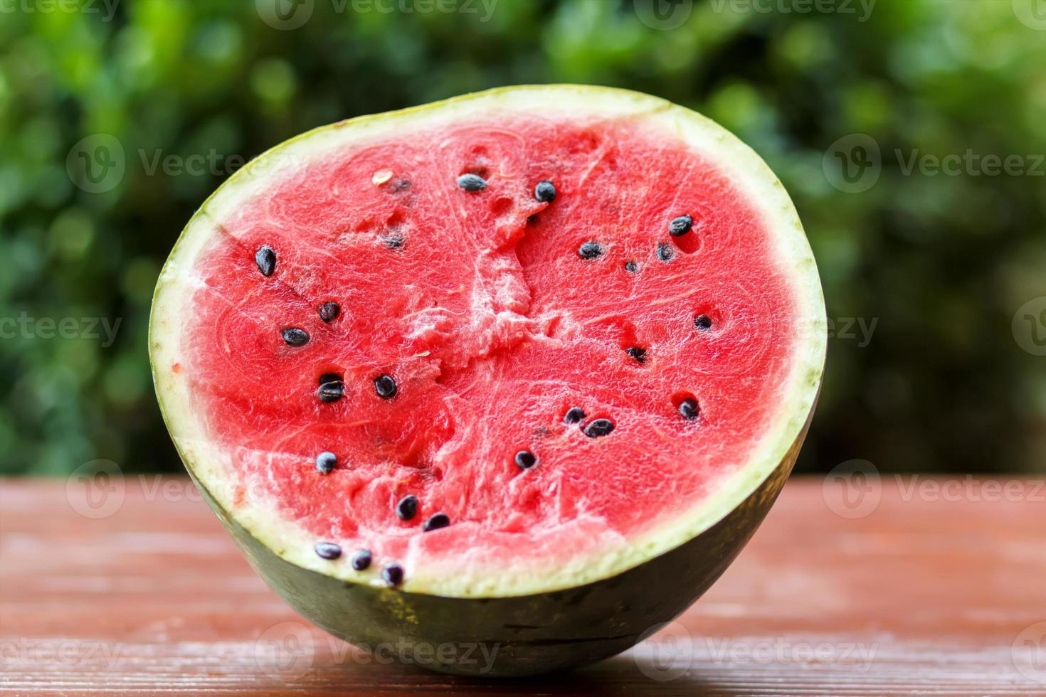 Fresh juicy watermelon against natural green background photo