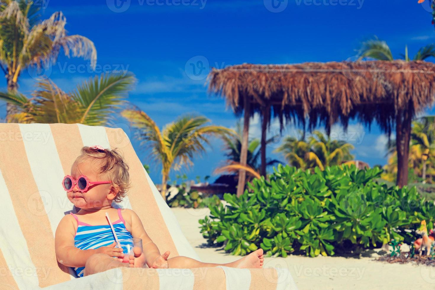 niña linda bebiendo jugo en playa tropical foto