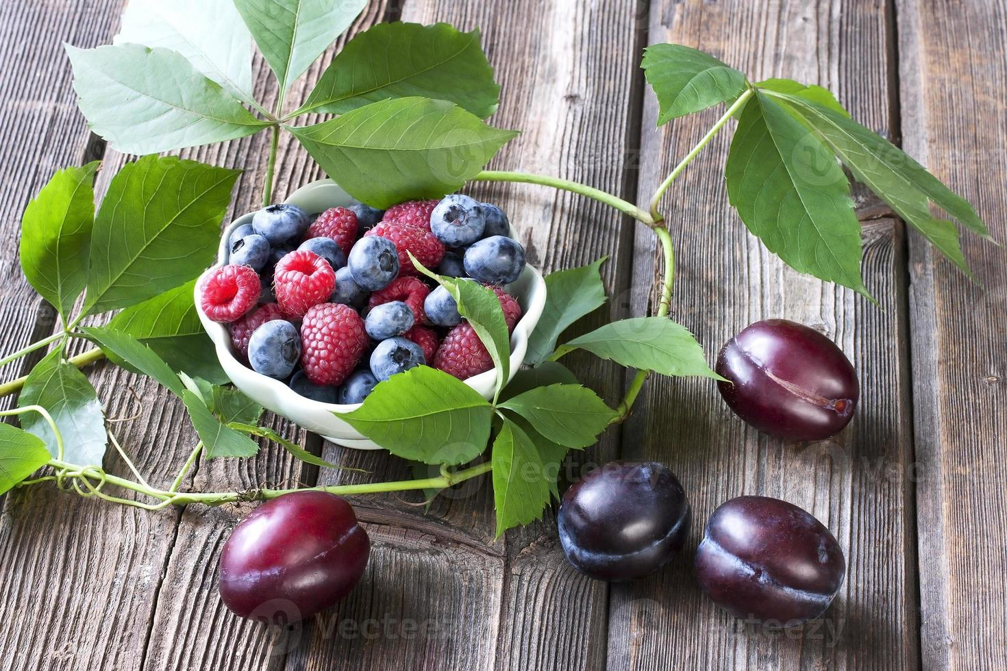 Fresh berries in a bowl on a wooden table photo