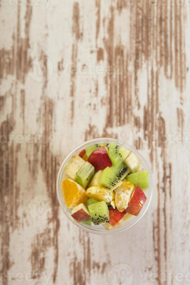 Vista aérea de ensalada de frutas sobre tabla de madera foto